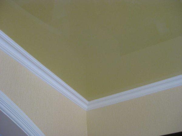 Потолочный плинтус прекрасно сочетается с натяжными потолками. Однако клеится он в этом случае только к стене.