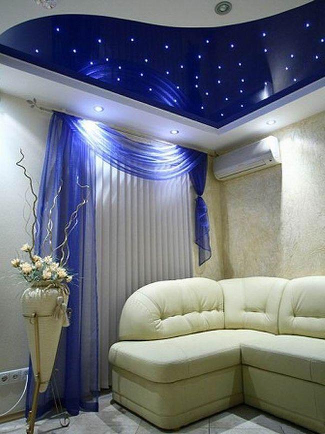 Натяжной потолок выигрышно подчеркивает стиль гостиной.