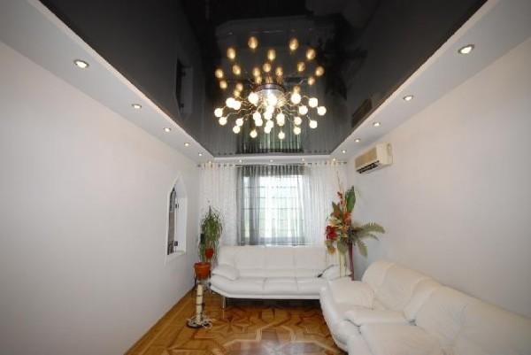 Потолочная люстра и черный глянцевый потолок в гипсокартонном коробе