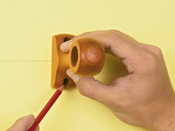 Размечаем отверстия кронштейна, перенеся их на стену