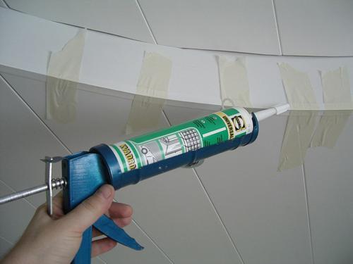 Уголок легко закрепить на силиконовый герметик. Малярный скотч зафиксирует его на время сушки.
