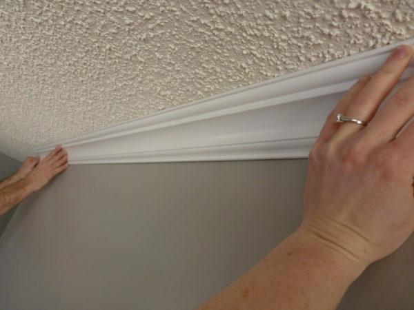 Для качественного приклеивания плинтус необходимо придавить к стенам и потолку