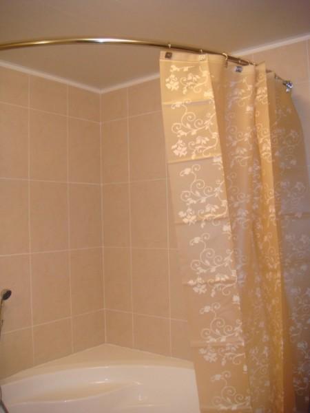 Дугообразный карниз идеально подойдет для закругленной угловой ванны.