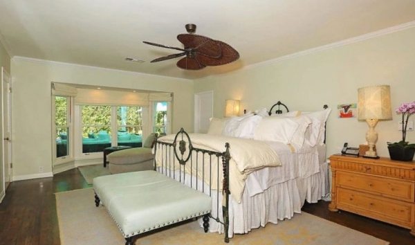 Спальня светлая, кровать с высоким матрасом и возле неё стоит широкий кожаный пуф