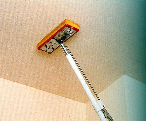 Смачивание поверхности потолка с помощью швабры