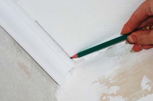 Прикладываем планку торцом к углу и отчерчиваем карандашом на потолке ее внутренний край.
