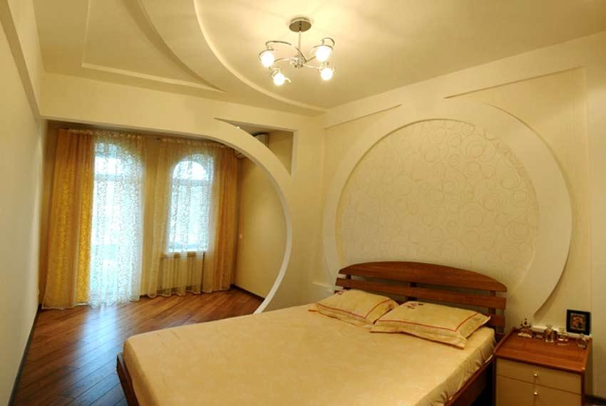 Фигурный потолок в спальне перекликается с дизайном стены