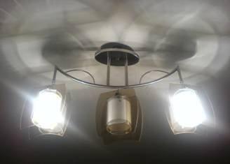 Когда рожки люстры смотрят вниз, тепло от ламп будет рассеиваться, не вызывая локального перегрева полотна потолка.