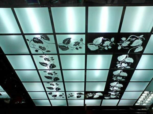 Этот потолок собран из подвесной системы Армстронг и нарезанного квадратами 60х60 матового стекла с наклеенной пленкой.