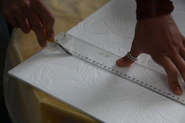 На фото – разрезка потолочной плитки ножом