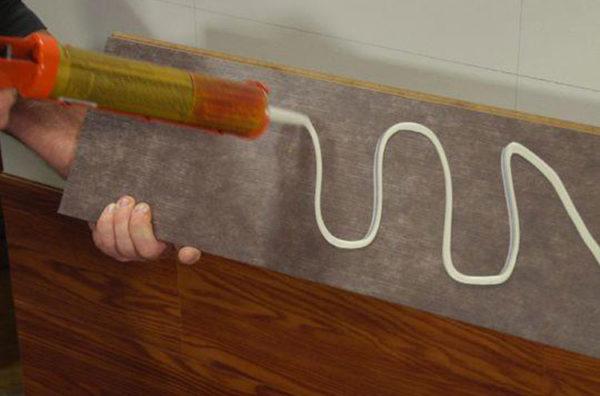 Нанесение клея на облицовочную панель.
