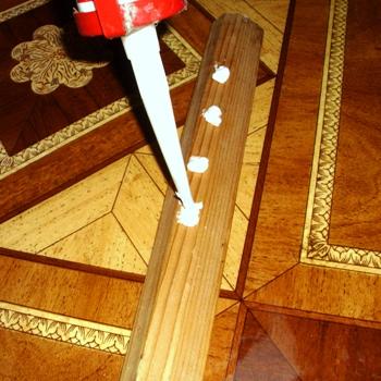 Нанесение жидких гвоздей на деревянный потолочный плинтус