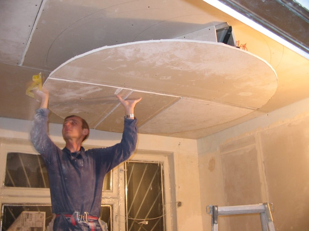 Одному человеку довольно неудобно и держать лист, и прикручивать его. Потолок из гипсокартона лучше монтировать вдвоем