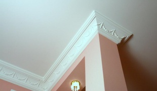 Неровный стык между потолком и стеной легко может скрыть с помощью плинтуса потолочного