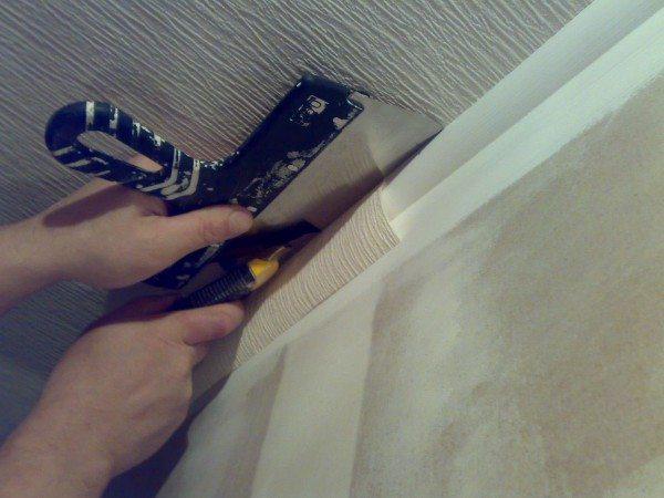 Обклейка потолка обоями: широкий шпатель пригодится и на этой стадии