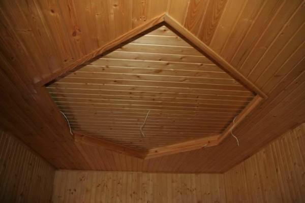 Потолок подшит простой деревянной вагонкой