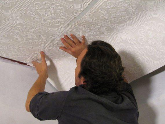 Полосы потолочных обоев наклеиваются исключительно встык, без нахлестов. Иначе включенная вечером люстра заставит каждый выступающий край отбросить тень на потолок