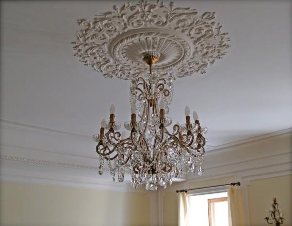 Потолок, выполненный в любом имперском стиле, всегда имеет множество элементов лепнины. Центральная потолочная розетка подчёркивает красоту люстры.