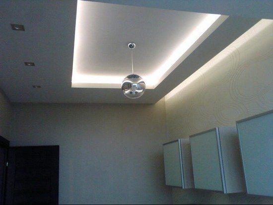 Большая кухня даёт возможность комбинирования люстры, точечных светильников и карнизов с подсветкой