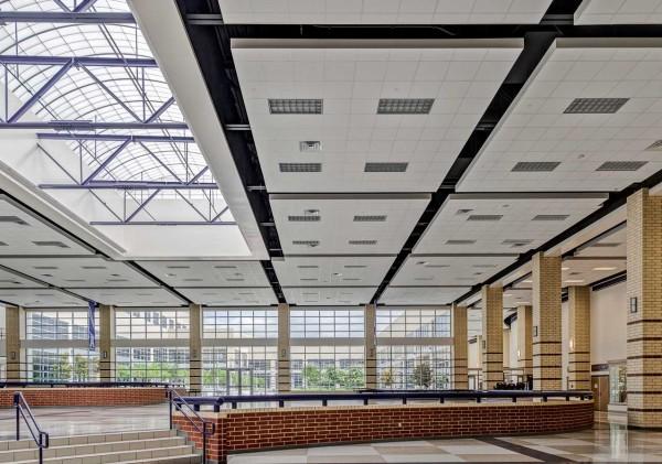 Диффузоры наряду с растровыми светильниками уложены в каркас кассетного потолка.