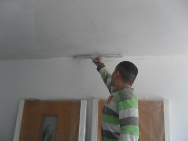 Устранить неровности потолка удобнее всего с помощью широкого шпателя