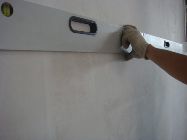 Правило прикладывается любой стороной в верхней части стены, между ним и основанием не должно быть значительных щелей
