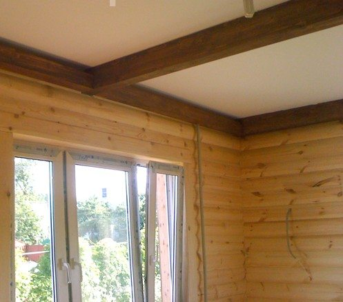 Темные балки с их натуральной текстурой выделяются на белом потолке, подчеркивая своеобразный стиль, а потолок будет при этом излучать максимум света
