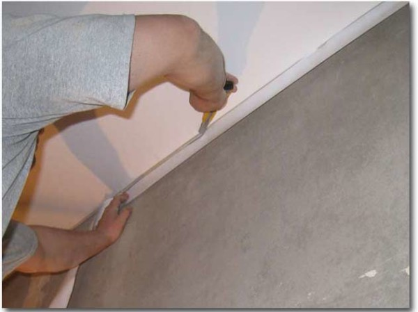Остатки полотнища срезаются строительным ножом