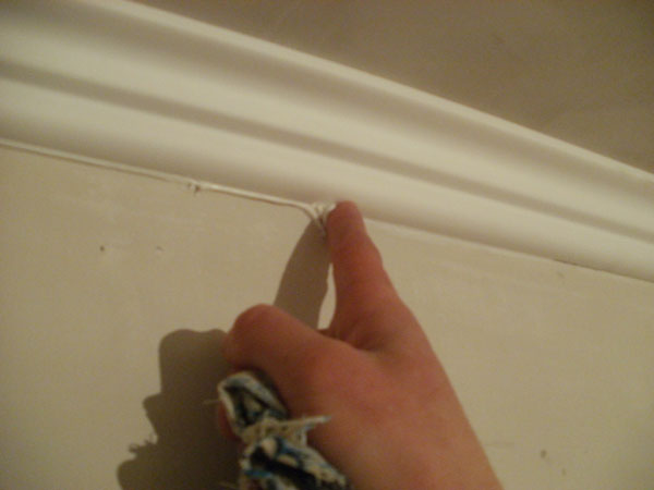 Замазка щелей между потолочным плинтусом и стеной